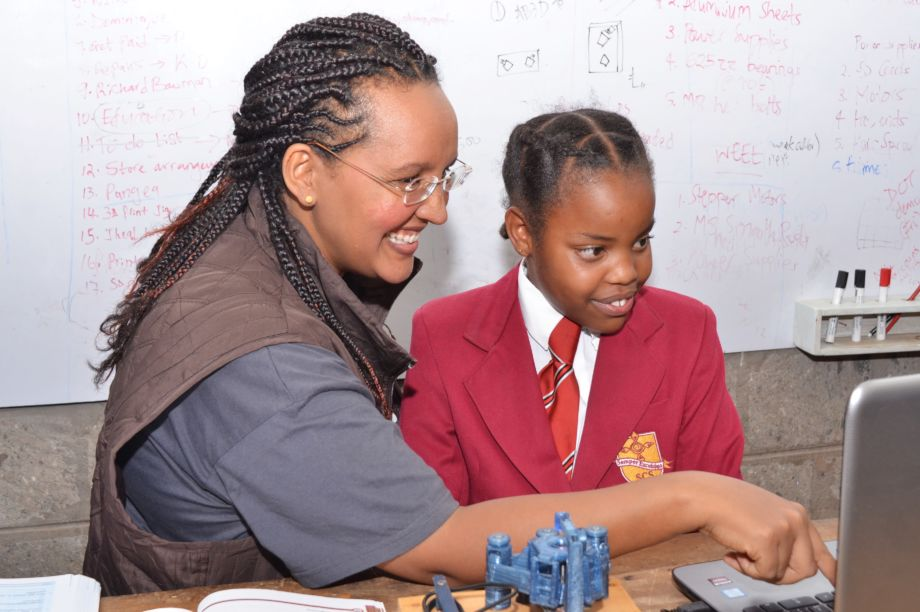 A woman and a young student use a computer together